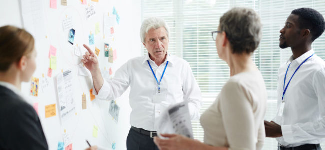 Multi-ethnic group of managers gathered together at modern boardroom and brainstorming on joint project, confident senior boss pointing at dry-erase board